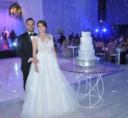 La pareja de enamorados posa para el lente fotográfico de Farah La Revista, junto a su pastel de bodas de estilo amarmolado, elaborado por Nadia Canahuati de Signatures Cakes