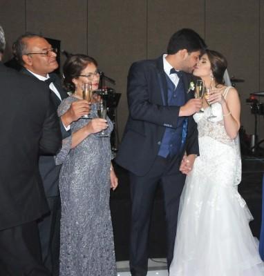 Una imagen adorable capturada durante el brindis de los recien casados, mientras los padres del novio son testigos de su amor...