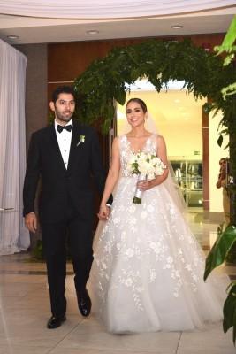 La hermosa novia lució un delicado modelo minimalista de la reconocida diseñadora Monique Lhuillier, mientras que el novio apostó por el clásico tuxedo.