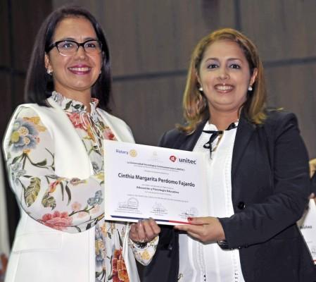 La Vice Presidenta de UNITEC entrega los diplomas de graduación.
